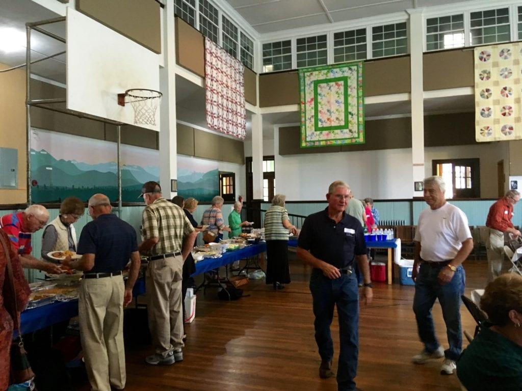 People enjoying covered dish meal at Sandy Mush School Reunion